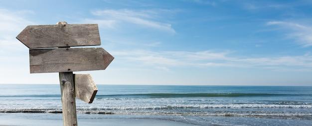 Opções de destinos de viagens de verão. direção sinal de estrada com flechas de madeira na praia e no mar