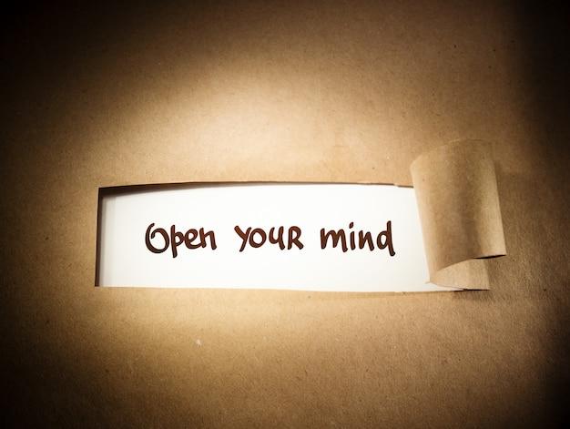 Open your mind aparecendo atrás de um papel marrom rasgado