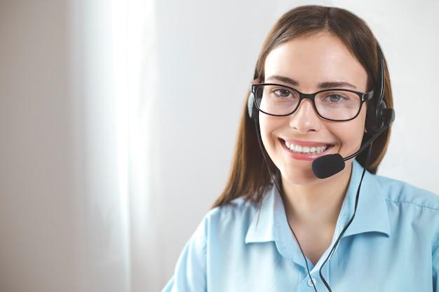 Operador amigável da jovem mulher do retrato que trabalha em um centro de atendimento.