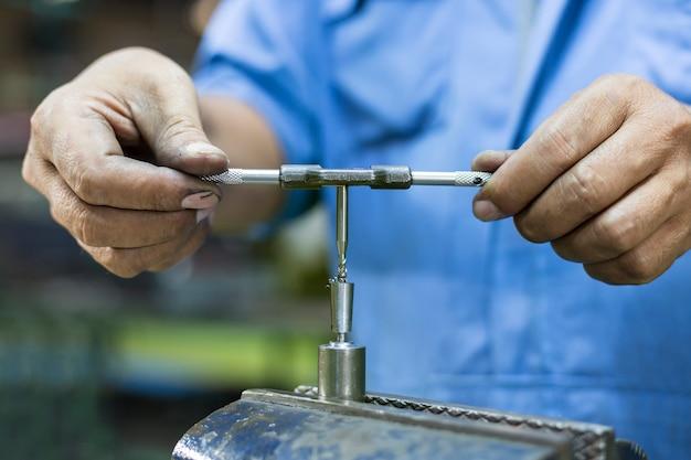 Operador batendo as peças do molde manualmente