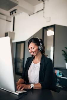 Operador bonito de sorriso do telefone do apoio dos jovens nos auriculares, no escritório.