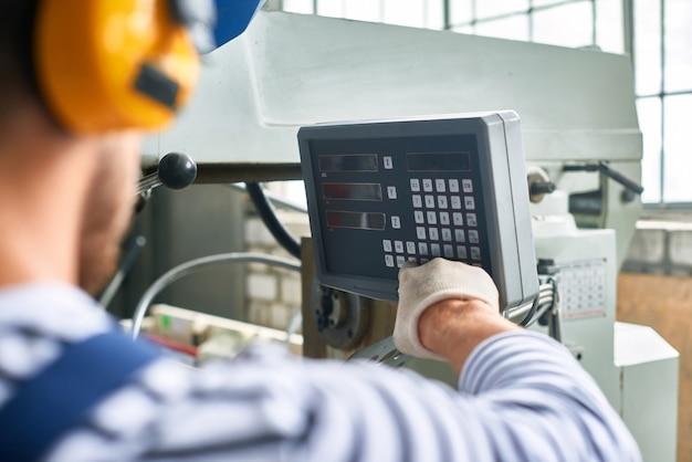 Operador configurando a máquina na fábrica