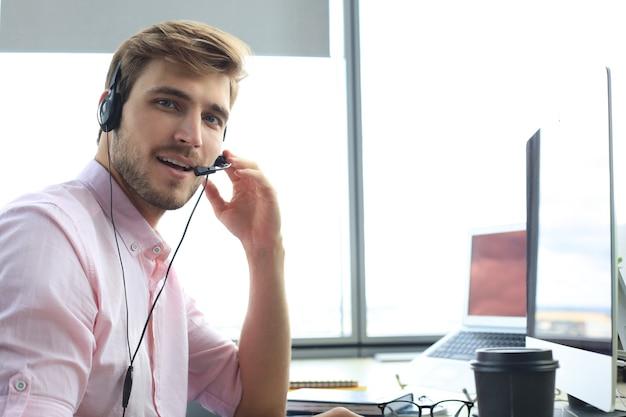 Operador de call center masculino jovem bonito amigável a sorrir.