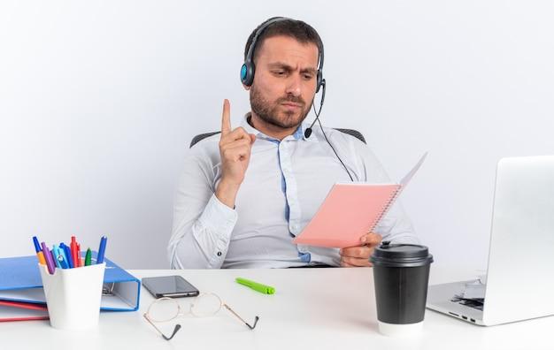 Operador de call center masculino jovem e triste usando fone de ouvido, sentado à mesa com ferramentas de escritório, segurando e lendo um caderno