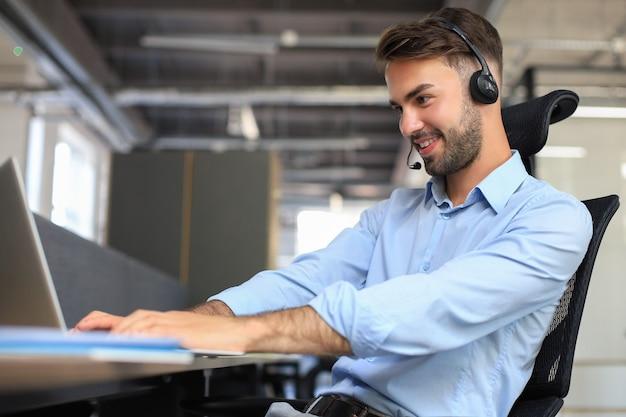 Operador de call center masculino sorridente com fones de ouvido sentado em um escritório moderno, consultando informações on-line em um laptop, procurando informações em um arquivo para ajudar o cliente.