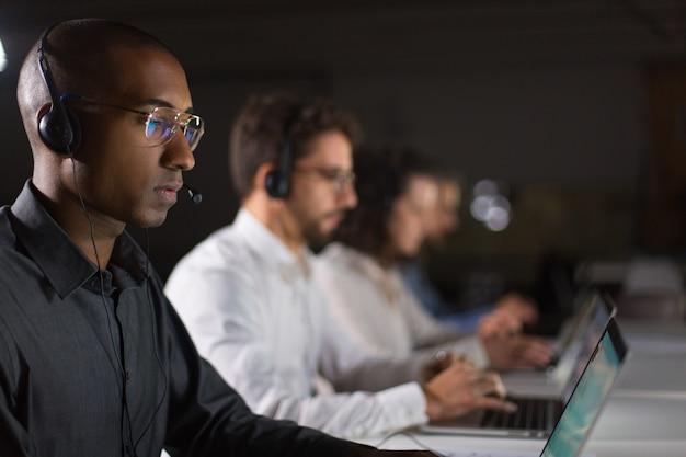 Operador de centro de chamada americano africano concentrado trabalhando