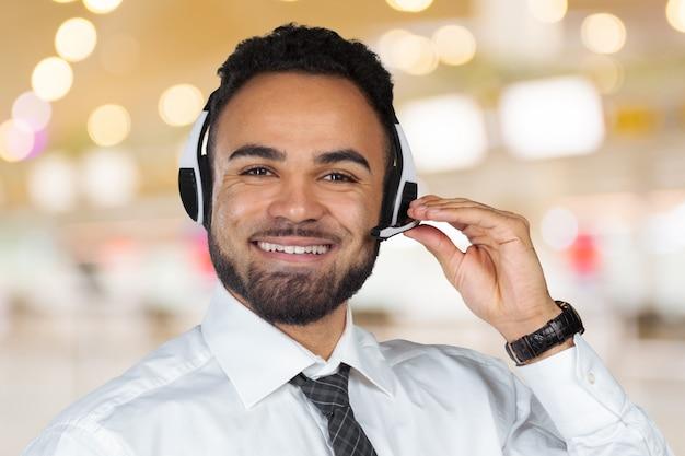 Operador de centro de chamada homem com fones de ouvido trabalhando