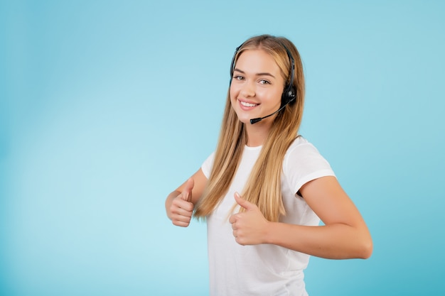 Operador de centro de chamada loira sorridente amigável com fone de ouvido isolado sobre o azul
