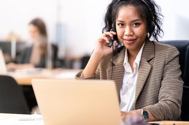 Operador de confiança amigável jovem adulto raça mista de mulher africana e asiática com fones de ouvido trabalhando em uma central de atendimento