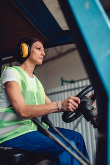 Operador de empilhadeira mulher dirigindo veículo