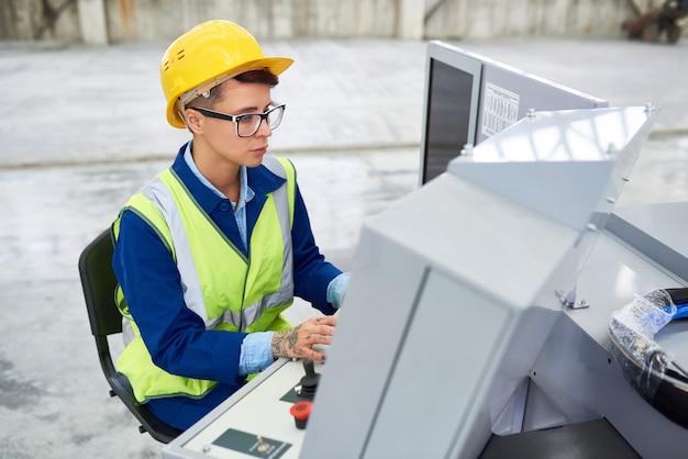 Operador de fábrica, trabalhando na máquina industrial