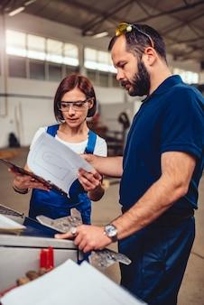 Operador de máquina cnc e engenheiro industrial, verificando o desenho do produto
