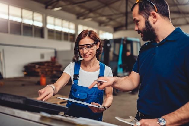 Operador de máquina cnc feminino, verificando o código do programa com supervisor