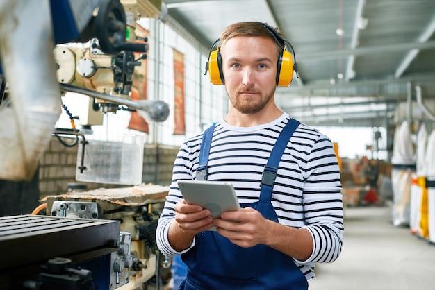 Operador de máquina moderna trabalhando na fábrica