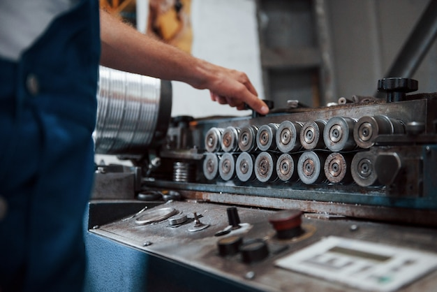 Operador de máquinas. homem de uniforme trabalha na produção. tecnologia industrial moderna.