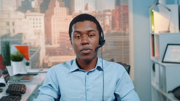 Operador de serviço ao cliente preto falando com cliente em call center
