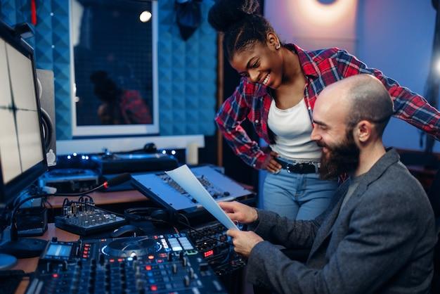Operador de som e cantora no painel de controle remoto no estúdio de gravação de áudio.