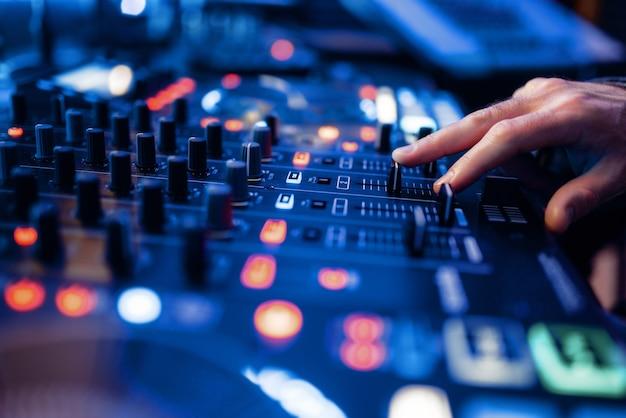 Operador de som mãos no painel de controle de volume no estúdio de gravação.