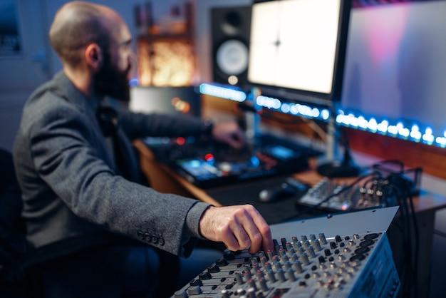 Operador de som no painel de controle remoto em estúdio de gravação de áudio.