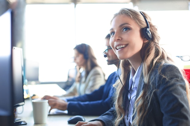 Operador de suporte ao cliente feminino com fone de ouvido e sorrindo, com colegas no fundo.