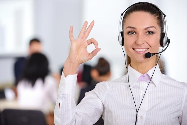 Operador de suporte ao cliente feminino com fone de ouvido e sorrindo.