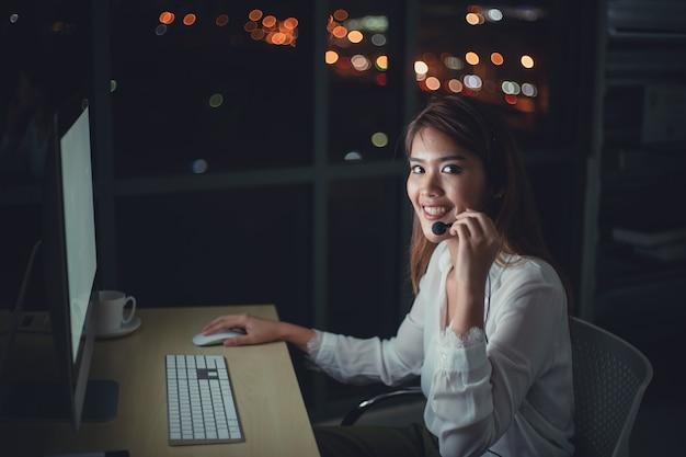 Operador de suporte ao cliente jovem empresário com fones de ouvido trabalhando até tarde da noite no escritório
