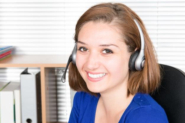 Operador de suporte ao cliente mulher com fone de ouvido e sorrindo