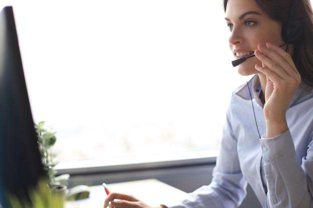 Operador de suporte ao cliente mulher com fone de ouvido e sorrindo.