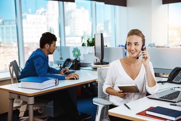 Operador de telefone de suporte feminino bonito jovem falando, consultoria, escritório