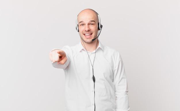 Operador de telemarketing apontando para a câmera com um sorriso satisfeito, confiante e amigável escolhendo você