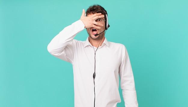 Operador de telemarketing chocado, assustado ou apavorado, cobrindo o rosto com a mão e espiando por entre os dedos