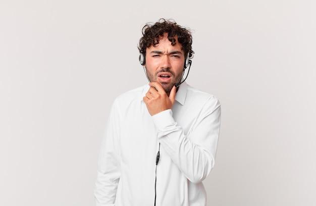 Operador de telemarketing com boca e olhos bem abertos e mão no queixo, sentindo-se desagradavelmente chocado, dizendo o quê ou uau