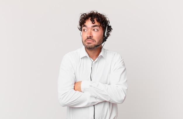 Operador de telemarketing encolhendo os ombros, sentindo-se confuso e incerto, duvidando com os braços cruzados e olhar perplexo