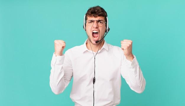 Operador de telemarketing gritando agressivamente com uma expressão de raiva ou com os punhos cerrados celebrando o sucesso