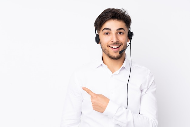 Operador de telemarketing homem árabe trabalhando com um fone de ouvido na parede branca, apontando o dedo para o lado