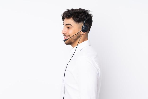 Operador de telemarketing homem árabe trabalhando com um fone de ouvido na parede branca, olhando para o lado