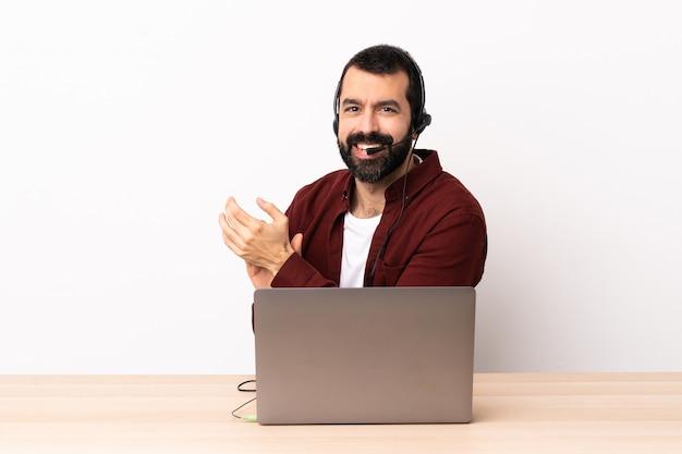 Operador de telemarketing homem caucasiano trabalhando com um fone de ouvido e com laptop aplaudindo