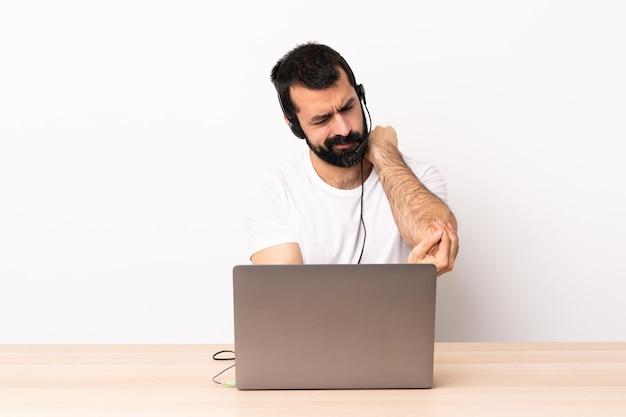 Operador de telemarketing homem caucasiano trabalhando com um fone de ouvido e com laptop com dor no cotovelo