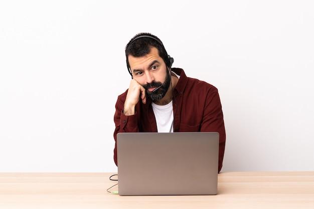 Operador de telemarketing homem caucasiano trabalhando com um fone de ouvido e com laptop com expressão cansada e entediada