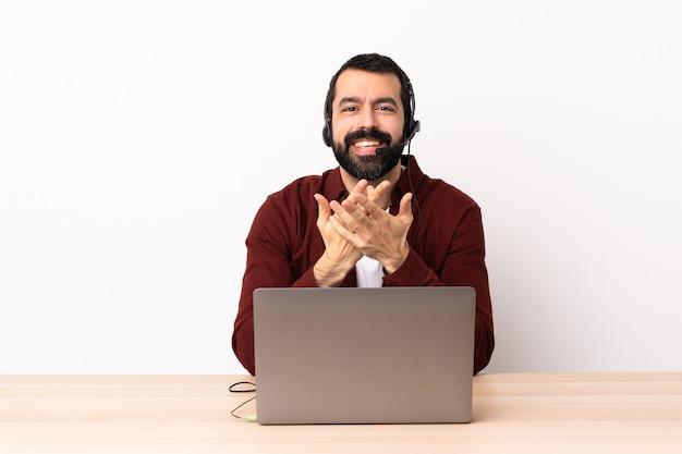 Operador de telemarketing homem caucasiano trabalhando com um fone de ouvido e com laptop rindo
