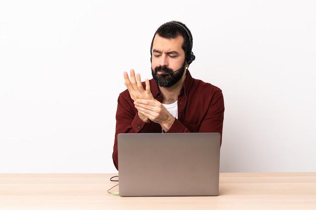 Operador de telemarketing homem caucasiano trabalhando com um fone de ouvido e com laptop sofrendo de dor nas mãos