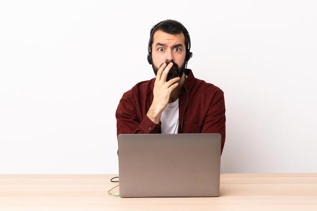 Operador de telemarketing homem caucasiano trabalhando com um fone de ouvido e com laptop surpreso e chocado enquanto olha bem.