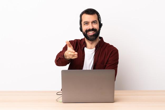 Operador de telemarketing homem caucasiano trabalhando com um fone de ouvido e com o laptop, apertando as mãos para fechar um bom negócio