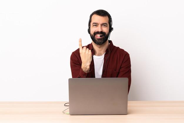 Operador de telemarketing homem caucasiano trabalhando com um fone de ouvido e com o laptop, fazendo o gesto vindo