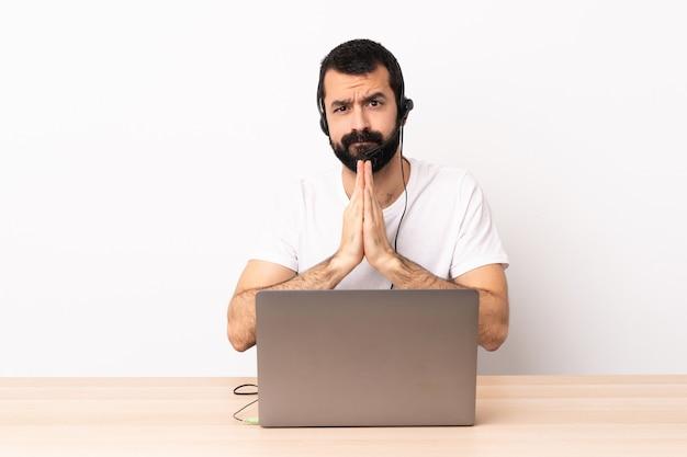Operador de telemarketing homem caucasiano trabalhando com um fone de ouvido e com o laptop mantém a palma da mão unida. pessoa pede alguma coisa.
