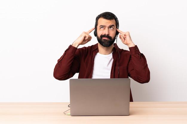 Operador de telemarketing homem caucasiano trabalhando com um fone de ouvido e com o laptop, tendo dúvidas e pensando.
