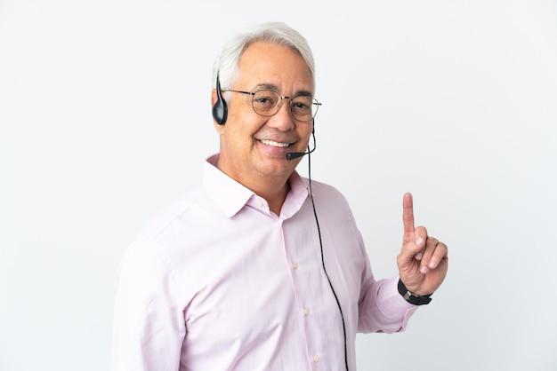 Operador de telemarketing homem de meia-idade trabalhando com fone de ouvido isolado, mostrando e levantando um dedo em sinal do melhor