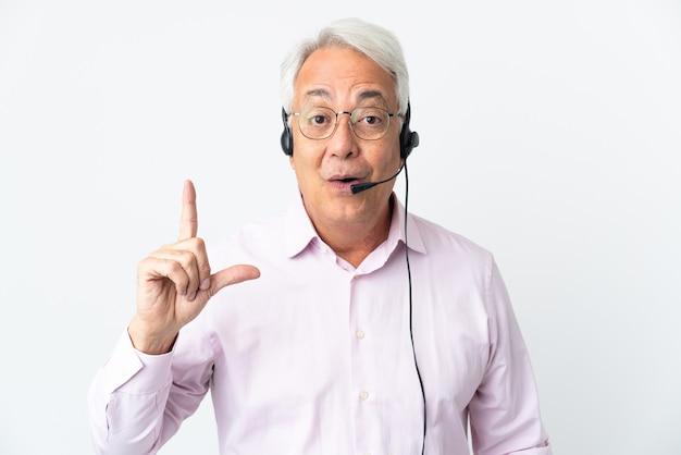 Operador de telemarketing homem de meia idade trabalhando com um fone de ouvido isolado em uma parede branca com a intenção de perceber a solução enquanto levanta um dedo