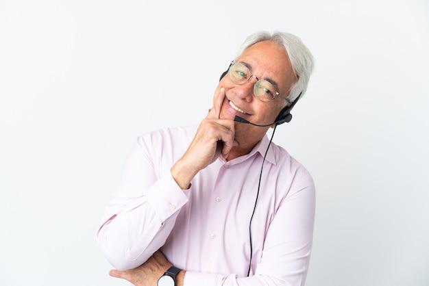 Operador de telemarketing homem de meia-idade trabalhando com um fone de ouvido isolado feliz e sorridente