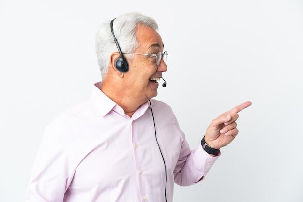 Operador de telemarketing homem de meia idade trabalhando com um fone de ouvido isolado no fundo branco com a intenção de perceber a solução enquanto levanta um dedo